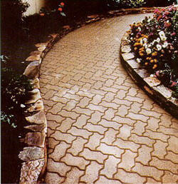 Winding walkway uses interlocking paving bricks against a stone retaining wall